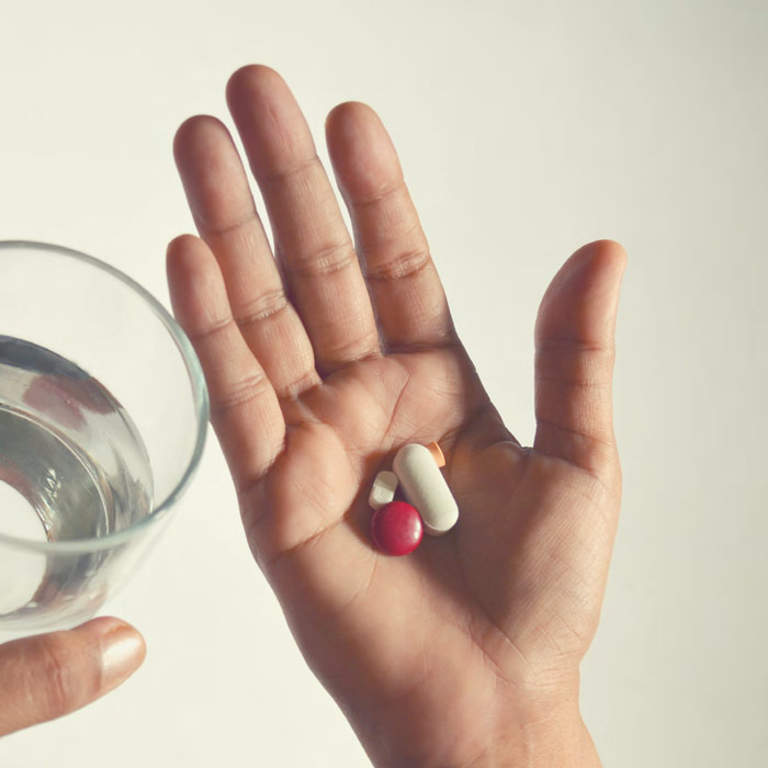 Hands Holding Pills And A Glass Of Water