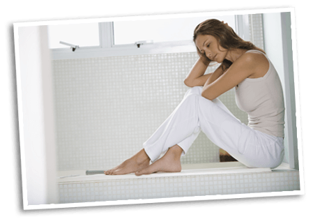 Woman looking forlorn holding her head while sitting by the bathtub