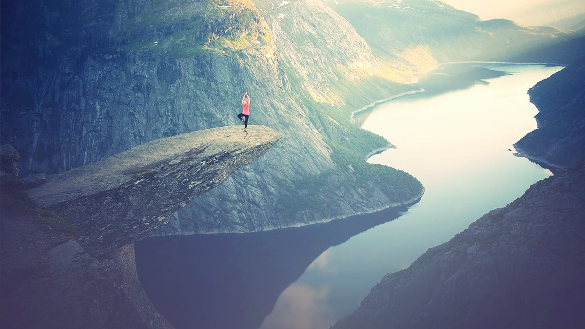 Person Doing Yoga On A Cliff Over A Lake