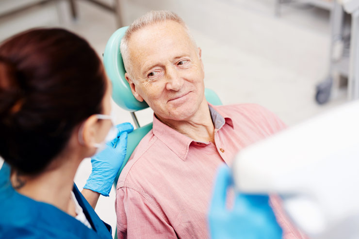 Senior man in dental chair with hygienist getting ready to examine him