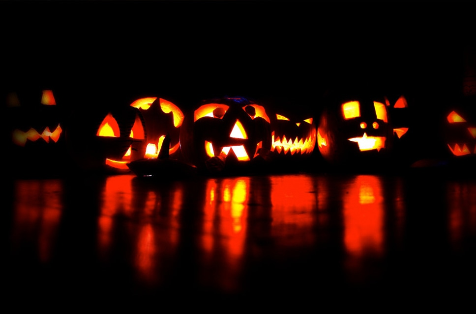 Several Carved Halloween Pumpkins With Candles In Them
