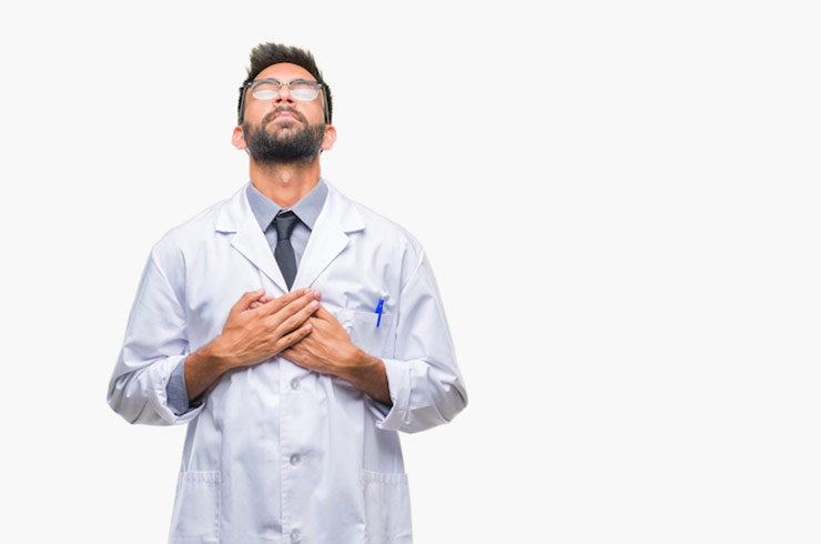Doctor With Hands Over Heart Looking Upward
