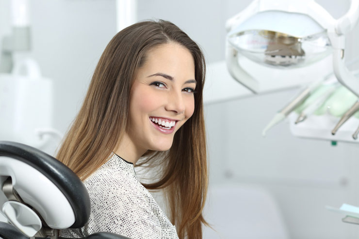 Happy Female Patient In Dental Chair