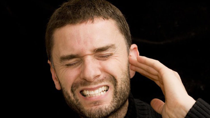 Man Holding His Ear And Wincing In Pain