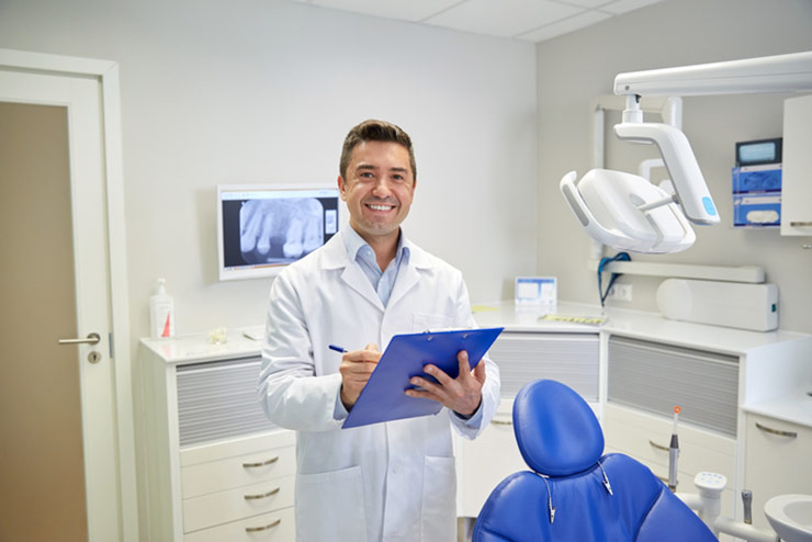 Smiling Male Doctor Holding Clip Board And Pen In Exam Room